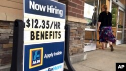 """FILE- A """"Now Hiring"""" sign is outside Aldi supermarket in Salem, New Hampshire, July 17, 2018. The Labor Department reports, Oct. 16, 2018, on job openings and labor turnover for August."""