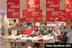 Pembeli yang mengenakan masker melihat-lihat pakaian di pusat perbelanjaan Senayan City pada hari pertama pembukaan kembali setelah ditutup selama berminggu-minggu karena pembatasan skala besar yang diberlakukan untuk mengekang penyebaran wabah virus coro