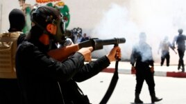 Police fire tear gas to break up a demonstration by the hardline Islamist group, Ansar al-Sharia May 19, in Kairouan, Tunisia.