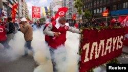 Para demonstran Turki di Lapangan Taksim, Istanbul berlarian setelah polisi menembakkan gas air mata, Kamis (1/5).