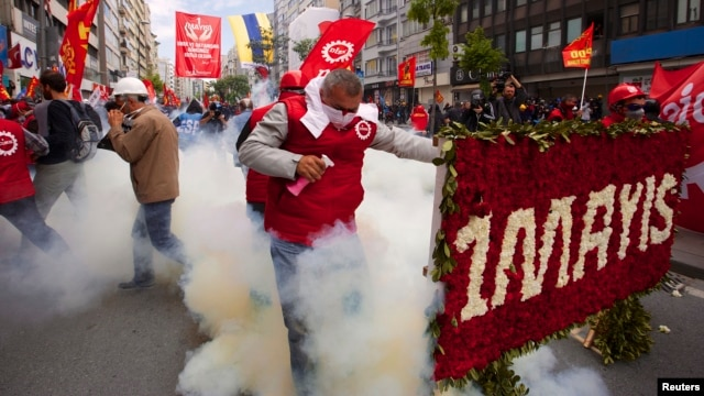A protester reacts as police fires tear gas during a May Day demonstration in Istanbul, May 1, 2014.