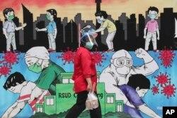 Seorang pegawai berjalan melewati mural bertema virus corona untuk menghormati tenaga kesehatan di RSUD Cengkareng Jakarta, Kamis, 24 Juni 2021. (Foto: AP)
