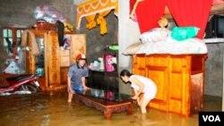 Warga Quang Binh, Vietnam, sedang memidahkan perabotan rumahnya yang dilanda banjir (18/10). Banjir telah melanda Vietnam sejak September lalu.