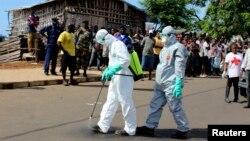 14일 시에라리온 프리타운에서 보건 관계자들이 에볼라로 사망한 환자의 시체를 처리한 후 몸을 소독하고 있다. 세계보건구기는 에볼라 발생 국가와 인전합 말리와 코트디부아르 등에 의료팀을 파견한다고 밝혔다.