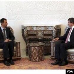 Menlu Turki Ahmet Dayutoglu (kanan) dalam pertemuannya dengan Presiden Suriah Bashar al-Ashad di Damaskus (8/9).
