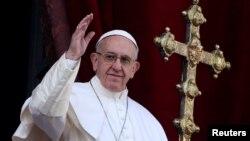 """Paus Fransiskus melambai kepada umat setelah menyampaikan pesan """"Urbi et Orbi"""" (kepada kota (Vatikan) dan seluruh dunia) dari balkon yang menghadap Lapangan Santo Petrus di Vatikan, 25 Desember 2016."""