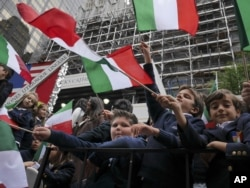 Schoolchildren wave Italian flags on a float in the Columbus Day parade in New York, Oct. 13, 2014. The parade is organized by the Columbus Citizens Foundation, and is billed as the world's largest celebration of Italian-American heritage and culture.