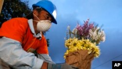 A worker places flowers on the tomb of Santos Etelvina Sontay, who died in the Cambray neighborhood mudslide, at the Santa Catarina Pinula cemetery on the outskirts of Guatemala City, Oct. 5, 2015.