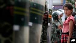 Uyg'ur qiz Xitoy harbiy politsiyachilari paradini tomosha qilmoqda, Urumchi, Shinjon, 2009-yil, 9-iyul