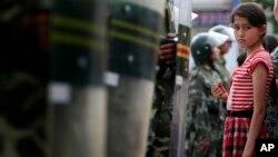 2009年7月9日一維吾爾族女孩在新疆省烏魯木齊觀看遊行被防暴警察攔住。