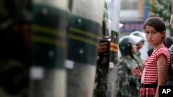 2009年7.5事件后,乌鲁木齐的一名维吾尔族女孩注视着一排中国防暴警察。(2009年7月9日)