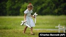 Стар Гай, 6 років, у місті Вако, Техас, допомагає замінити хрести на могилах тим, хто загиб під час протистояння членів «Храму народів» з федеральними агентами.