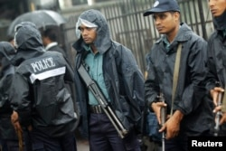 FILE - Police officers stand guard in front of the gate of International Crimes Tribunal (ICT) before a verdict against Bangladesh Jamaat-e-Islami chief Motiur Rahman Nizami in Dhaka, June 24, 2014.