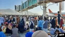 Afghans crowd at the tarmac of the Kabul airport on Aug. 16, 2021, to flee the country as the Taliban were in control of Afghanistan after President Ashraf Ghani fled the country and conceded the insurgents had won the 20-year war.