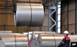 FILE - A worker moves steel coils at the Thyssenkrupp steel factory in Duisburg, Germany, April 27, 2018. German reaction to the announcement of U.S. tariffs being placed on steel and aluminum imports was among the fiercest in Europe.