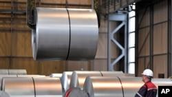 جرمنی کی ایک فیکٹری میں فولاد کی چادروں کے رول بنائے جا رہے ہیں۔ 27 اپریل 2018