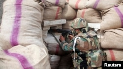 지난 2월 시리아 정부군이 알레포 아르드-알함라를 탈환한 가운데, 한 군인이 무기를 겨누고 있다. (자료사진)