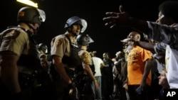 Policías y manifestantes se enfrentaron a lo largo de la avenida West Florissant, en Ferguson, Missouri, el lunes, 10 de agosto de 2015.