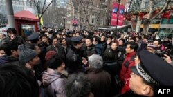 Cảnh sát kêu gọi người dân rời khỏi 1 địa điểm tụ họp trước 1 rạp chiếu phim ở Thượng Hải, Trung Quốc, Chủ Nhật 20/2/2011