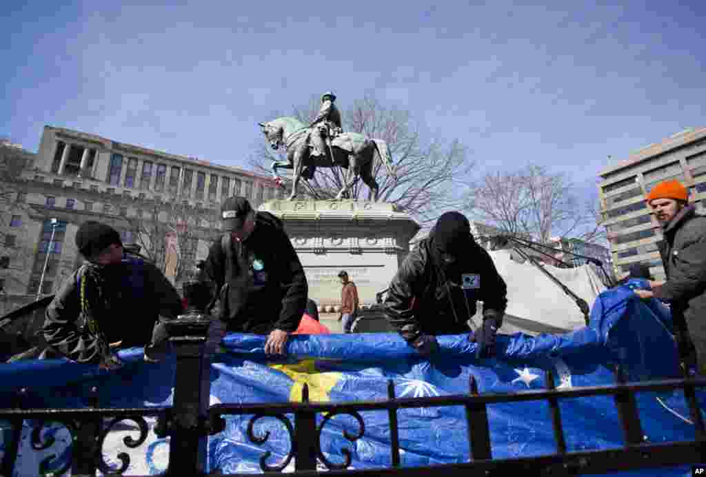 "Occupy DC demonstrators raise a tarp to form a symbolic ""tent"" over the statue in McPherson Square in protest of expected enforcement of no-camping regulations. (Alison Klein/VOA)"