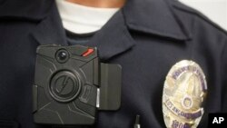 File - Los Angeles Police officer demonstrates on-body camera for media in Los Angeles, California.