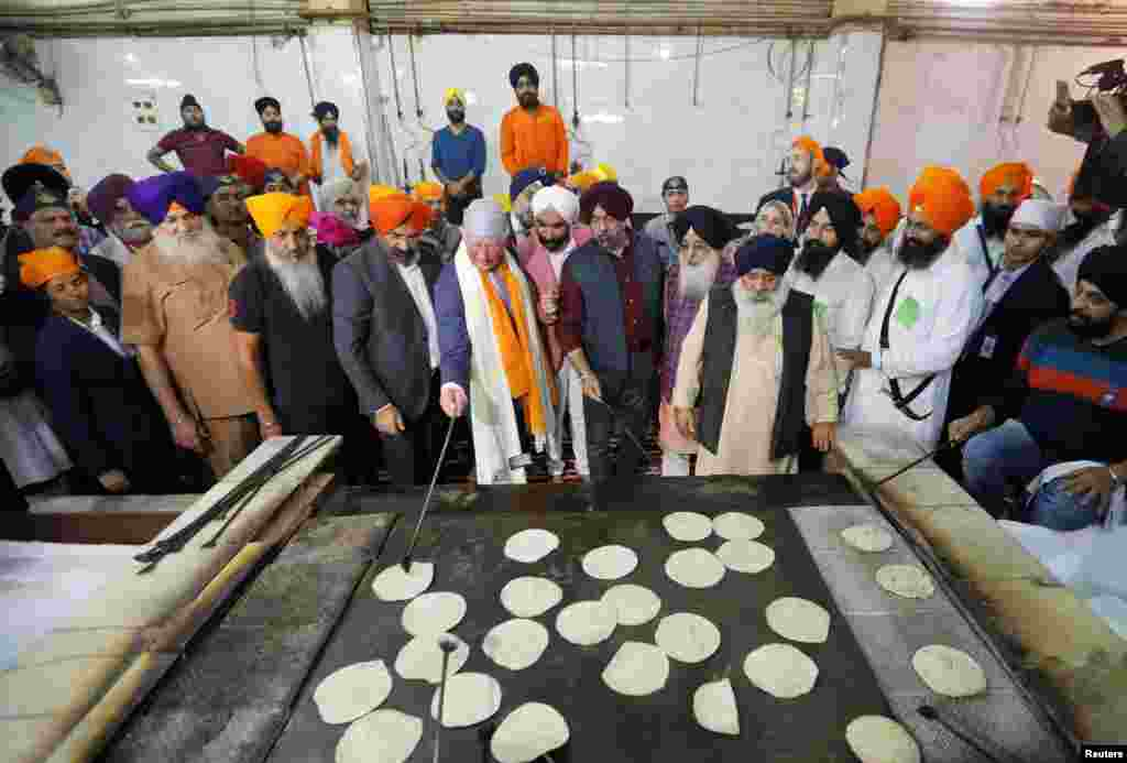 Britain's Prince Charles prepares bread at a community kitchen during his visit to a Gurudwara (Sikh temple) in New Delhi, India.