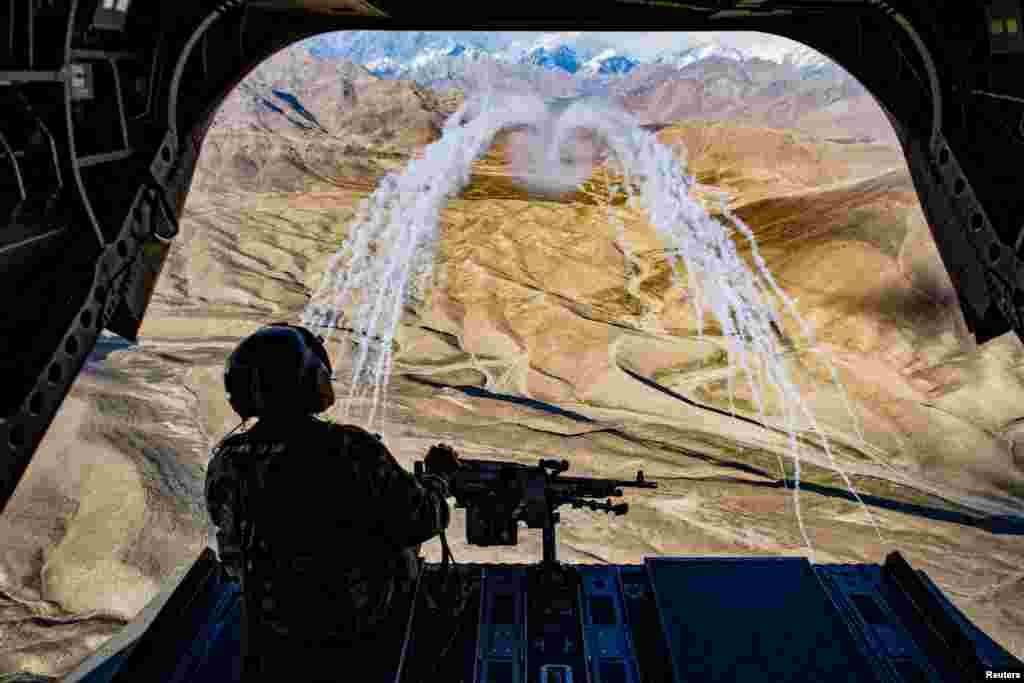 ប្រធានក្រុមទាហានអាមេរិកម្នាក់ជិះលើឧទ្ធម្ភាគចក្រCH-47F Chinook ដើម្បីអង្កេតមើលការហ្វឹកហាត់តាមអាកាសនៅប្រទេសអាហ្វហ្គានីស្ថានកាលពីថ្ងៃទី១៤ មីនា ២០១៨។