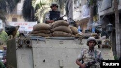 A soldier stands next to an armored personnel carrier (APC) near the Egypt stock exchange near Tahrir Square in Cairo, Sept. 17, 2013.