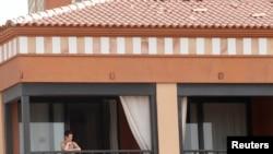 Una mujer observa desde la ventana de la habitación del hotel donde las autoridades españolas los mantienen encerrados debido a dos casos positivos del nuevo virus.