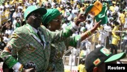FILE: Zimbabwe's President Robert Mugabe and his wife Grace arrive to address the final rally of his ZANU-PF party in Harare, July 28, 2013.