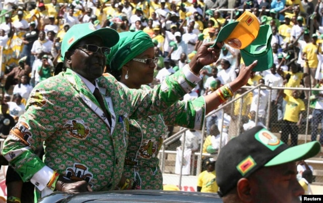Zimbabwe's President Robert Mugabe and his wife Grace arrive to address the final rally of his ZANU-PF party in Harare, July 28, 2013.