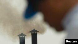 Một người đàn ông đi ngang qua ống khói của một nhà máy ở ngoại ô Hà Nội.