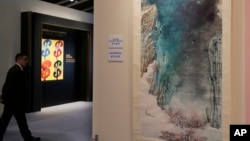 """FILE - A man walks past the painting """"Peach Blossom Spring"""" by Chinese artist Zhang Daqian during a preview for the Sotheby's Spring Sales in Hong Kong, April 1, 2016."""