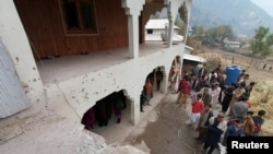 Locals gather near a house which was damaged, according to them, by cross-border shelling, in Neelum Valley, in Pakistan-administrated Kashmir, Nov. 13, 2020.