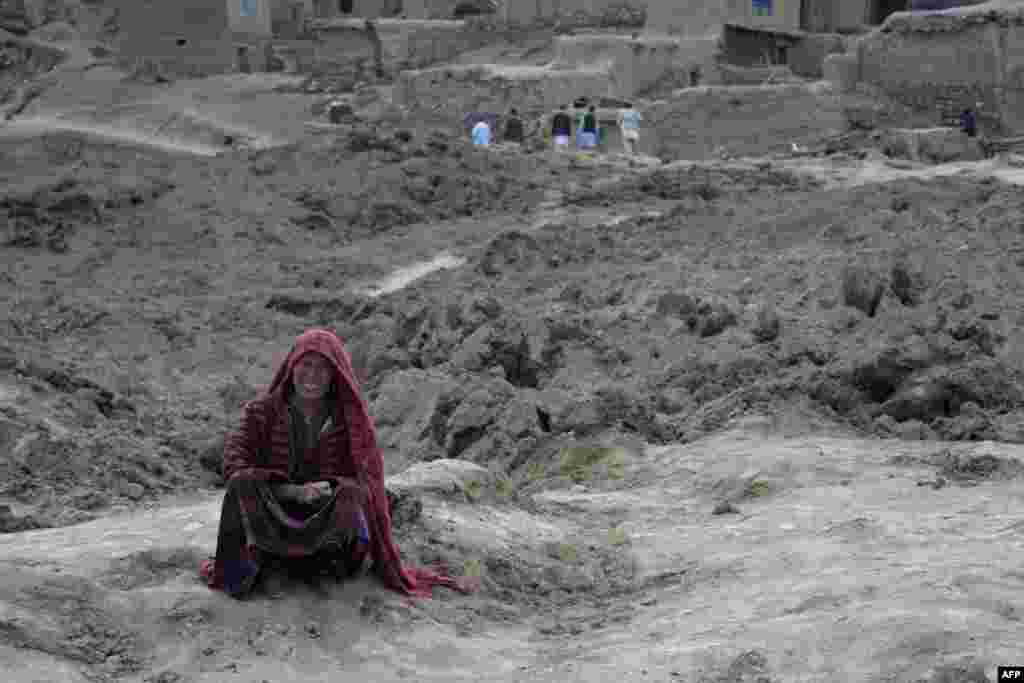 An Afghan villager cries as she sits on top of a mud field in Argo district of Badakhshan province after a massive landslid buried a village. Rescuers searched in vain for survivors after a landslide buried Aab Bareek village, killing 350 people and leaving thousands of others feared dead amid warnings that more earth could sweep down the hillside.