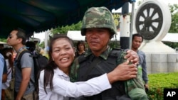 A pro-government demonstrator embraces a Thai soldier during a cleanup operation at a pro-government demonstration site on the outskirts of Bangkok, Thailand, May 23, 2014.