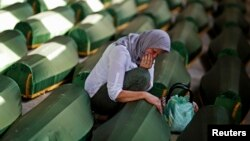 A Bosnian woman cries at a coffin of her relative, one of 173 of newly identified victims from the 1995 Srebrenica massacre.
