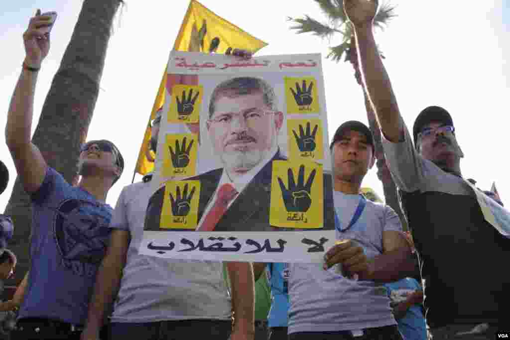 Protesters hold a poster of ousted Egyptian President Mohamed Morsi during a march in Maadi, southern Cairo, Sept. 20, 2013. (Hamada Elrasam for VOA)