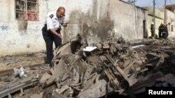 伊拉克安全部队一名成员2013年4月15日在巴格达以北250公里远的基尔库克的一处遭受汽车炸弹攻击的地点进行调查。