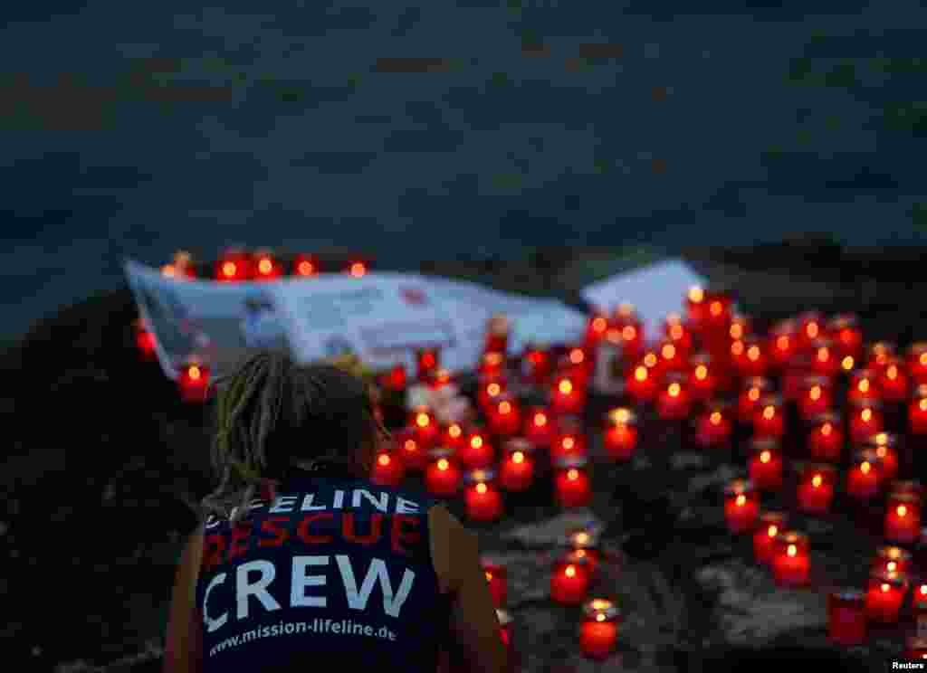 A crew member of charity ship MV Lifeline takes part in a vigil to commemorate migrants who have lost their lives whilst crossing the Mediterranean Sea, and to insist that such loss of life is never normalised in light of some European governments enactin