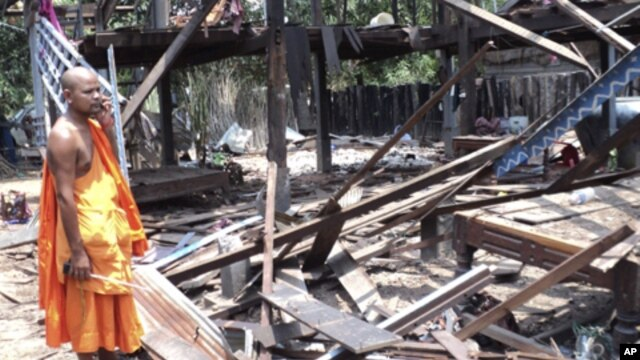 A Cambodian Buddhist monk watches a house damaged by a rocket during Monday night's armed clash near the disputed border area between Cambodia and Thailand in Kork Morm village, Udor Meanchey province, Cambodia, Tuesday, April 26, 2011. Thai and Cambodian