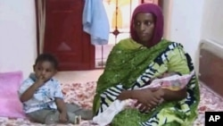 FILE - Meriam Ibrahim, sitting next to Martin, her 20-month-old son, holds the newborn daughter she gave birth to in jail in May at a prison in Khartoum, Sudan.