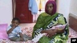 易卜拉欣抱着她的苏丹狱中出生的女儿,旁边坐着的是她18个月大的儿子(资料照片)