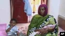 易卜拉欣抱著她的蘇丹獄中出生的女兒,旁邊坐著的是她18個月大的兒子(資料照片)