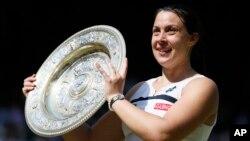 Marion Bartoli dari Perancis berpose dengan trofi kejuaraan Wimbledon setelah mengalahkan Sabine Lisicki dari Germany dalam final putri di London (6/7). (AP/Stefan Wermuth)