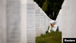A woman cries at a graveyard, ahead of a mass funeral in Potocari near Srebrenica, Bosnia and Herzegovina July 11, 2020.