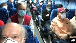 Các công dân Mỹ được đưa lên xe buýt để ra sân bay về nước hôm 17/2.