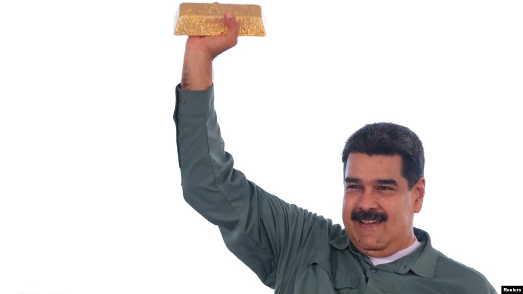 Tổng thống Venezuela Nicolas Maduro cầm một thỏi vàng trong khi gặp gỡ các đại diện của ngành khai khoáng năm 2017.