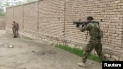 A member of Afghan security forces fires towards Taliban positions on a street in Kunduz, Afghanistan, Aug. 31, 2019, in a still image taken from video.