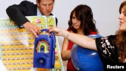Britain's Prince Harry is shown a wind up radio by UNICEF personnel Alison Tilbe (C) and Hilde Johnson at UNICEF offices during his visit to New York June 26, 2010.